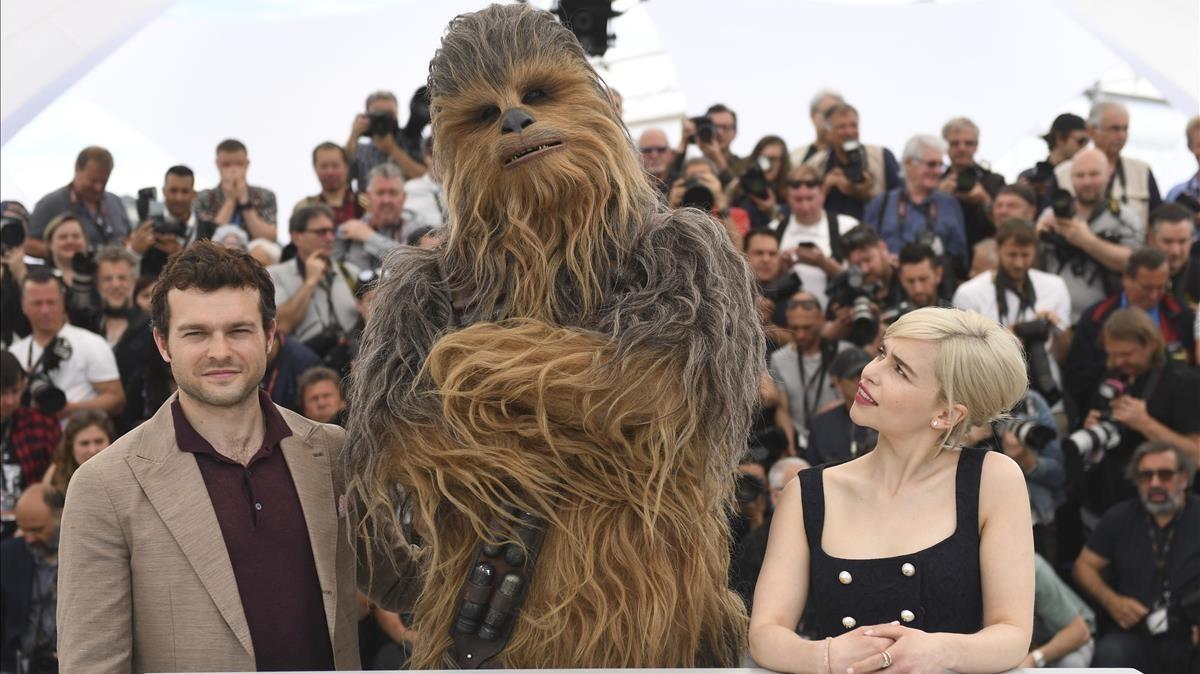 Los actores Aiden Ehrenreich y Emilia Clarke, con una persona disfrazada de Chewbacca, en Cannes.