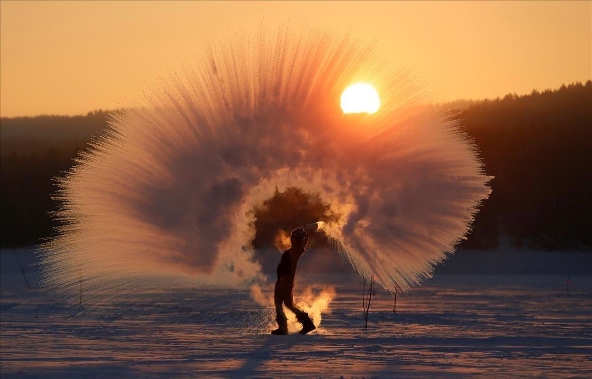 Olesya Ushakova, entusiasta de los deportes al aire libre, arroja agua caliente al aire bajo cero mientras participa en el Dubak Challenge, una tendencia de las redes sociales que se traduce en un intenso desafío frío que es recientemente popular en Rusia durante la puesta de sol fuera de la ciudad de Siberia.