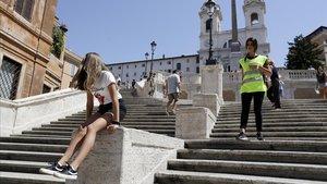 Un agente de policía informa a una turista que está prohibido sentarse en la escalinatade la plaza de España de Roma