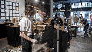 Trabajadores de la firma de moda Scalpers preparan este domingo el establecimiento para la reapertura comercial de mañana lunes.