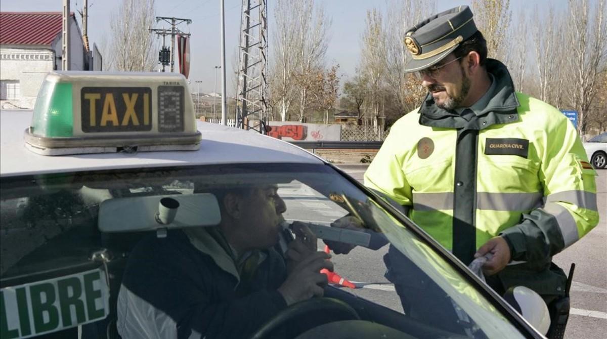Un conductor se somete a una prueba de alcoholemia ante un agente de la Guardia Civil, en Madrid.