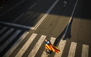 Un hombre camina con su 'estelada'antes del cierre de campaña en Barcelona.