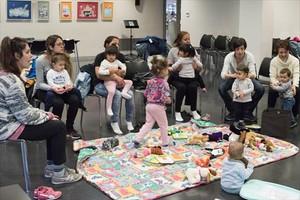 Madres con sus niños pequeños en una de las sesiones de juegos de falda que coordina Rosa Ferrer en la biblioteca Zona Nord.