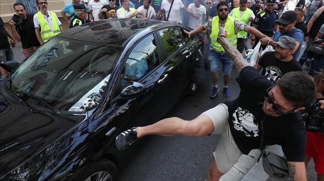 Un participante en la manifestación de taxistas da una patada a un Cabify