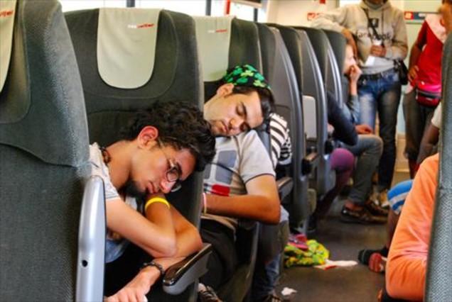Refugiados y migrantes se suben a un tren tras cruzar la frontera de Macedonia.