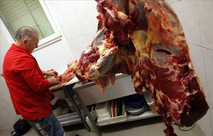 Un carnicero prepara carne de caballo en una tienda de Marsella.