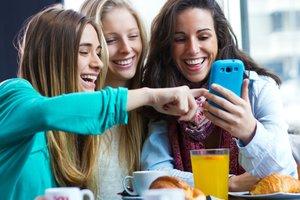 Tres chicas se divierten con el teléfono móvil.