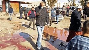 Ciudadanos libios comprueban los daños en el lugar del atentado, en Bengazi, el 24 de enero.
