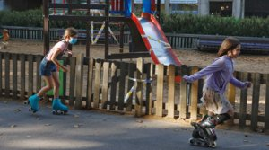 Dos niñas patinan junto a un parque con los columpios precintados, en Barcelona, el 17 de junio.