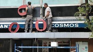 Dos operarios desmontan el cartel del Cosmos.