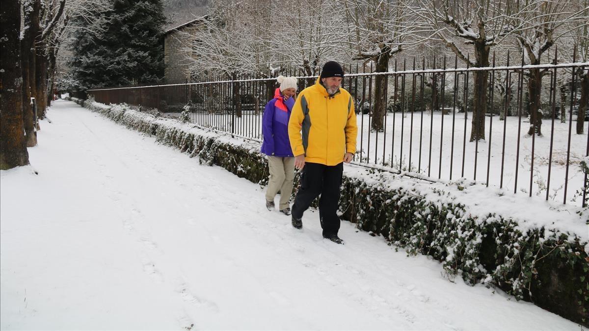 Dos vecinos de Camprodón paseando ante un paisaje nevado.