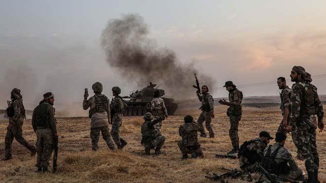 Soldados turcos y combatientes sirio, en las afueras de Manbij, cerca de la frontera.