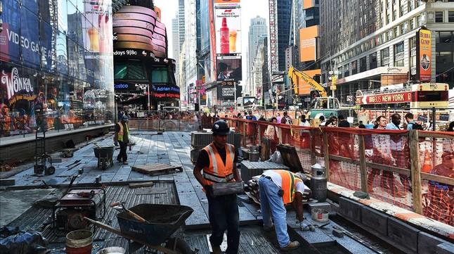Empleados trabajan en obras de una acera y carretera en Times Square (New York).