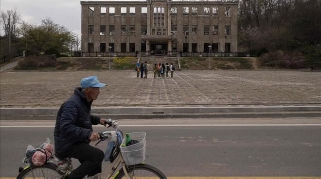 Un hombre pasa junto a la antigua sede del Partido Comunista