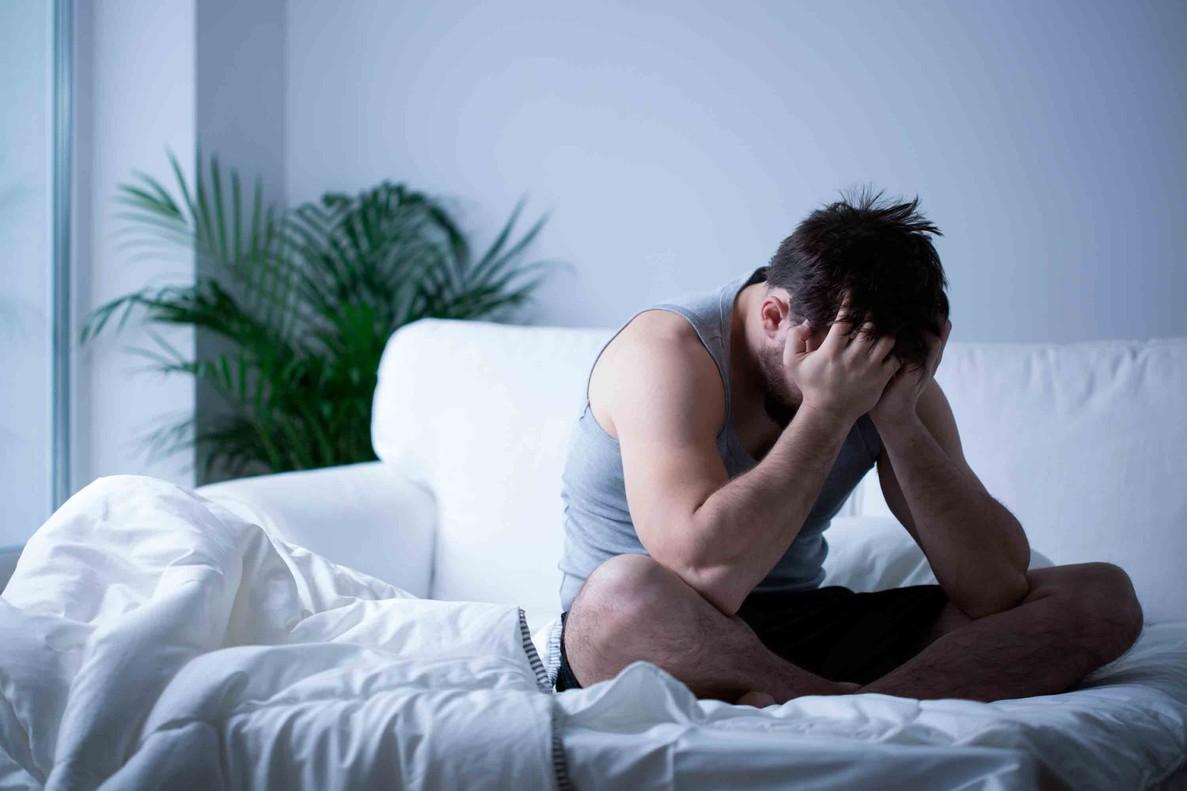 Hombre sentado en la cama con ansiedad.