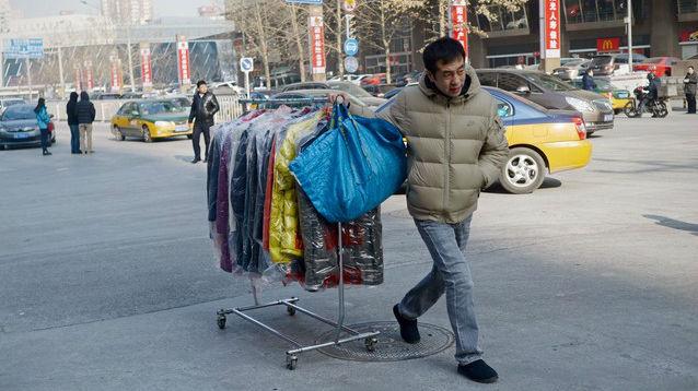 Un hombre transporta vestidos en una calle de Pekín.