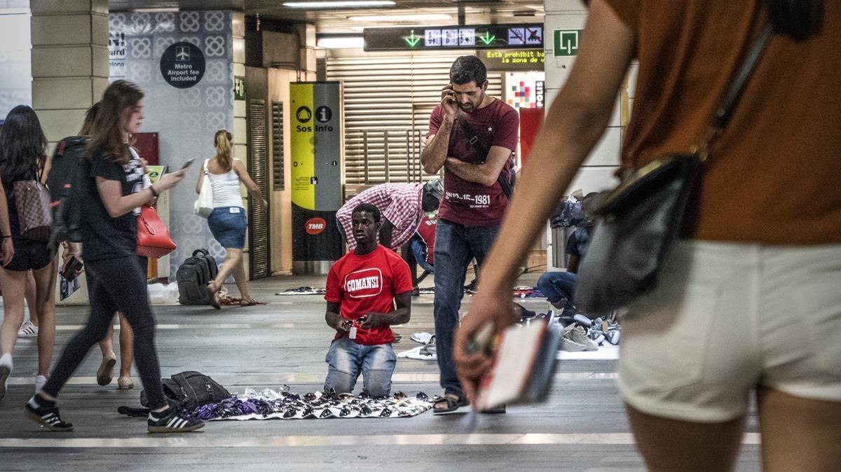 Manteros en el vestíbulo de Rodalies de plaza de Catalunya.