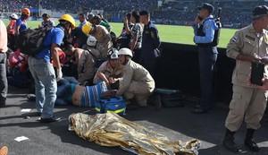 Las asistencias médicas atienden a varios heridos cerca de uno de los dos fallecidos dentro del estadio.