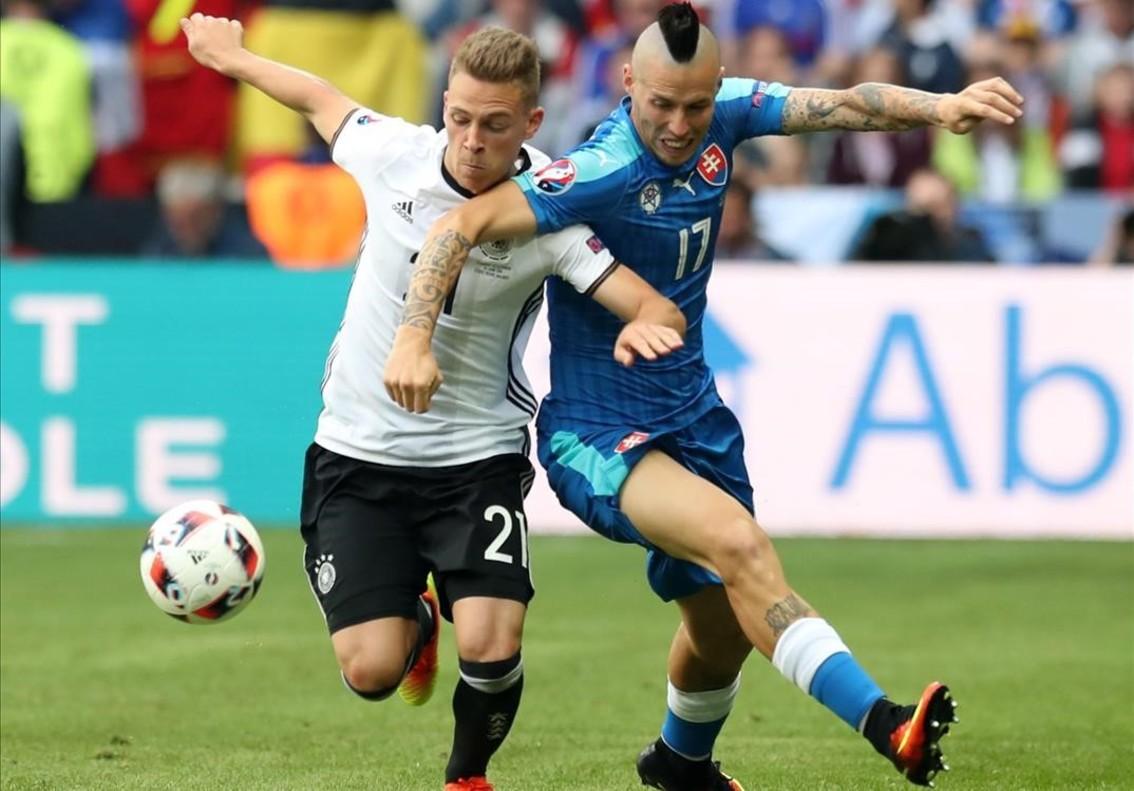 El lateral alemán Kimmich disputa el balón con el eslovaco Hamsik.
