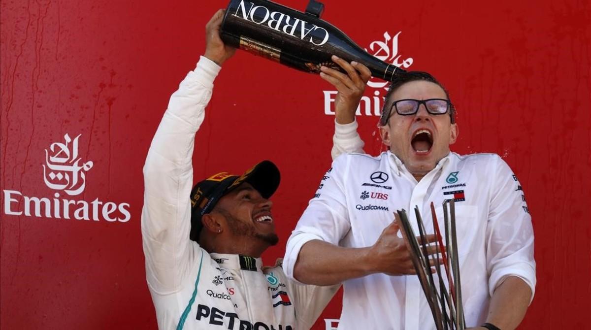 Lewis Hamilton ducha en champaña a Peter Bonnington, uno de sus ingenieros en el equipo Mercedes.