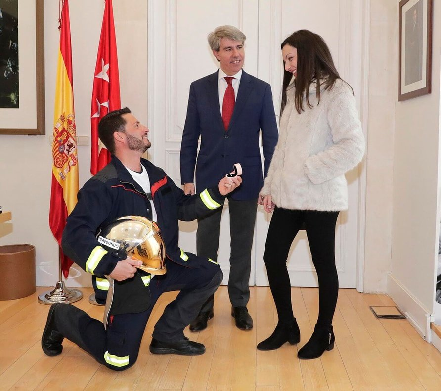 El nuevo bombero, en el momento de pedir la mano de su novia, delante del presidente madrileño, Angel Garrido.