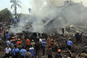 Miembros de los servicios de rescate indonesios trabajan en la búsqueda de víctimas tras estrellarse un avión militar de transporte del Ejército indonesio en Medán.