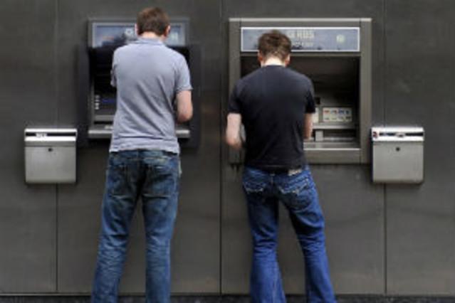 Dos hombres operando en un cajero automático.