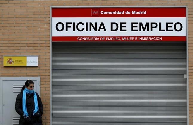 Una mujer espera ante una oficina de empleo.