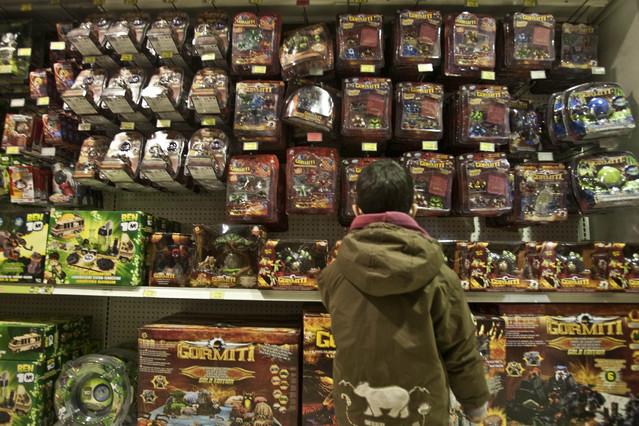 Un nen mira una prestatgeria plena de joguines en una botiga de Barcelona.