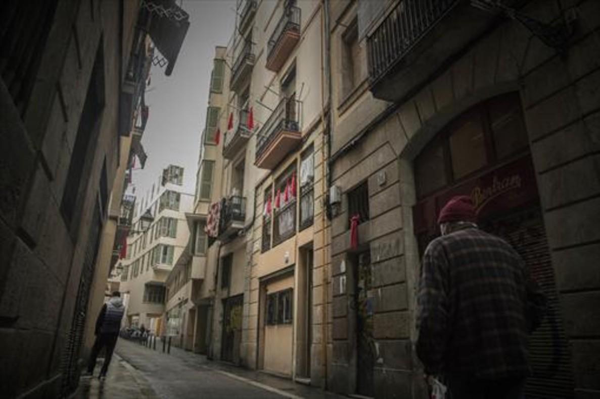 Pañuelos rojos cuelgan en las fachadas de los edificios de la calle de En Roig, en el Raval, para protestar por la venta de droga en la zona.