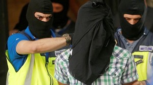 Police lead away a suspect from an apartment block during a raid in which they arrested a 32-year-old Moroccan they said was highly radicalised, in Madrid, Spain June 21, 2017. REUTERS/Juan Medina