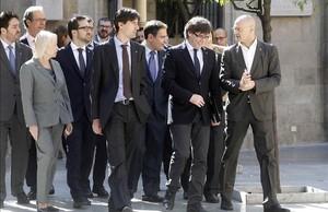 El 'president' Carles Puigdemont conversa con el 'conseller' d'Exteriors, Raül Romeva, junto a los delegados catalanes en el extranjero.