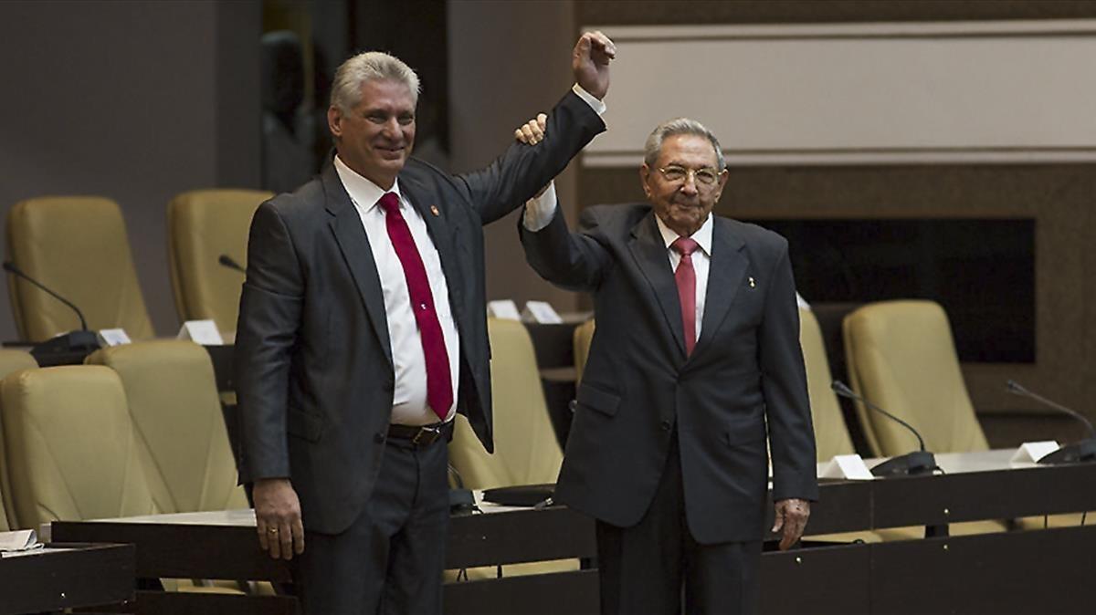 Raúl Castro (derecha) levanta el brazo del nuevo presidente de Cuba, tras ser nombrado oficialmente por la Asamblea Nacional, en La Habana, el 19 de abril.