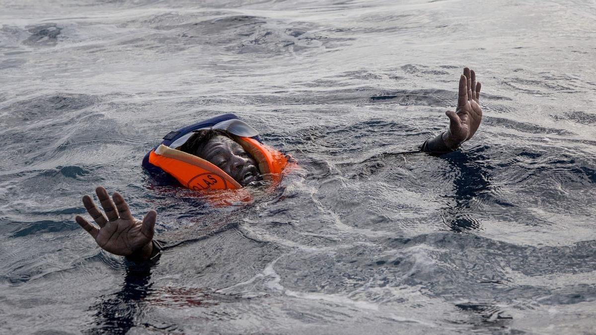 Un refugiado espera ser rescatado tras naufragar en el Mediterráneo.