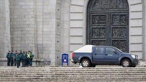 Un grupo de guardias civiles de los que han realizado preparativos esta mañana en la basílica del Valle de los Caídos, habla a la puerta de la basílica de la Santa Cruz junto a un coche de operarios de Patrimonio Nacional.