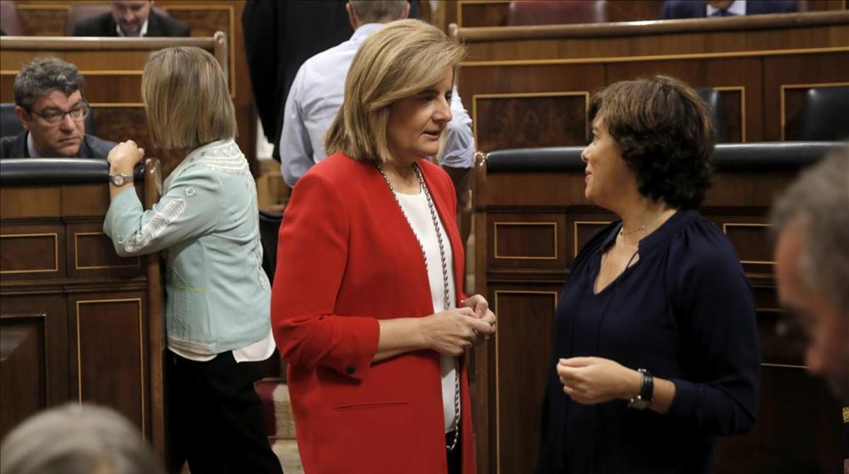 La ministra de Empleo, Fátima Báñez, conversa con la vicepresidenta, Soraya Sáenz de Santamaría, en el pleno del Congreso de los Diputados.
