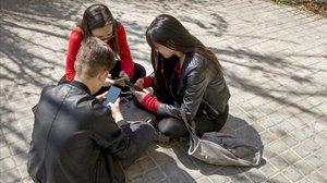 Tres adolescentes usando las redes sociales.