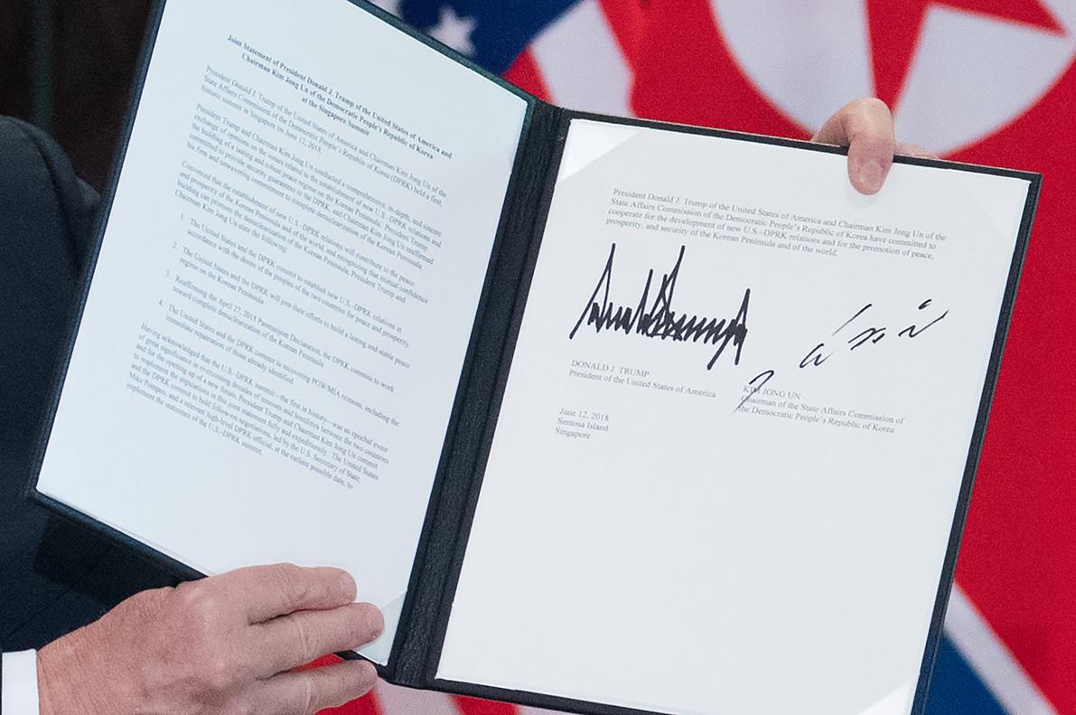 Trump muestra la declaración conjunta que él y Kim Jong-un han firmado en Singapur.