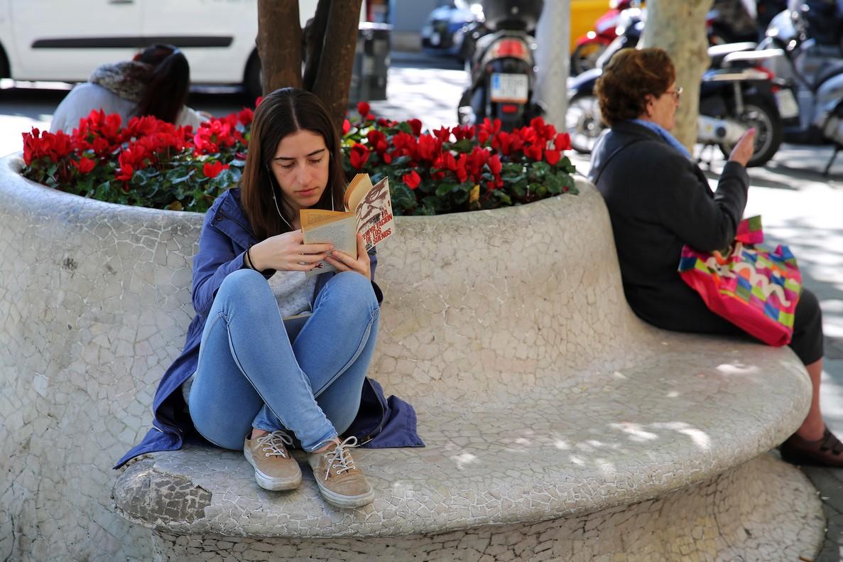 Una joven disfruta de la lectura en un banco del paseo de Gràcia de Barcelona.