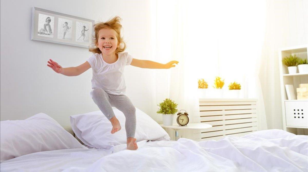 Una niña pequeña salta feliz en la cama.