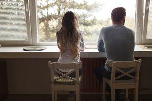 Una pareja sentada mirando por la ventana.