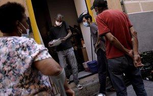 Un momento del reparto cotidiano de comida a vecinos necesitados del barrio madrileño de Lavapiés.