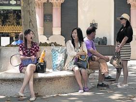 Uns turistes xinesos descansen de les compres al passeig de Gràcia, ahir.