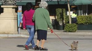 Una mujer mayor pasea con su cuidadora por una calle de Barcelona.