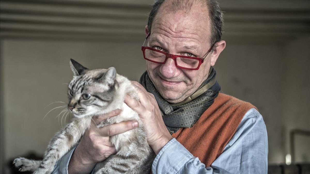 Marcos Isamat, con la gata Manolita, en su casa en Gràcia.