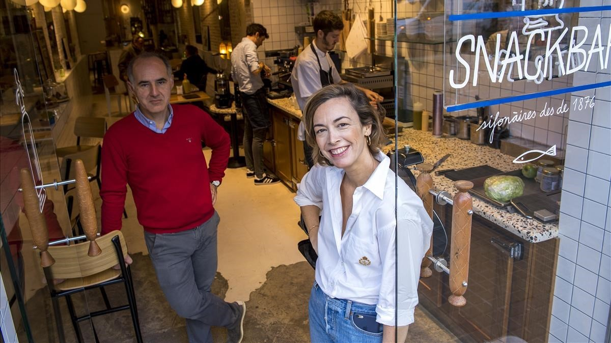 Olivier Guilland y Helena Garriga, en la puerta de El Sifó, con un cocinero y el barista trabajando detrás.