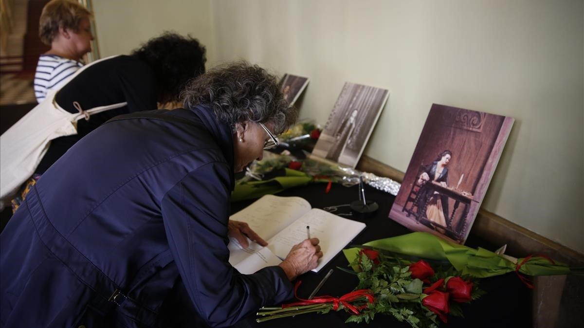 Dos mujeres se despiden de Caballé firmando en el libro de condolencias del Liceu, ayer.