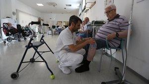U sanitario atiende a un usuario en el centro de día de Santa Coloma de Gramenet, el pasado viernes.