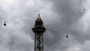Las cabinas del teleférico del puerto de Barcelona y un helicóptero que lo sobrevuela contrastan con el cielo cubierto con el que hoy ha amanecido Barcelona