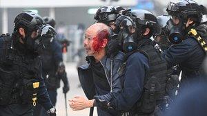 La policía se lleva a un manifestante herido en Hong Kong.